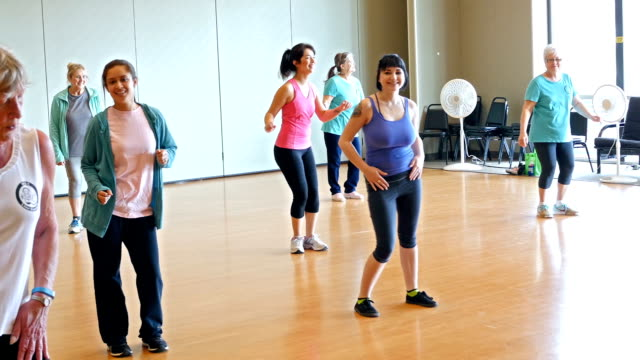 Diverse mixed age group of women doing dance aerobics in exercise class video