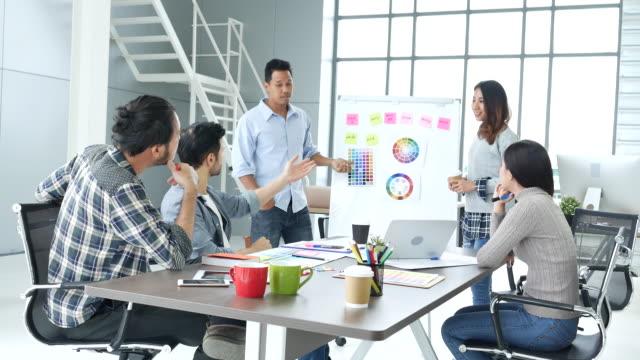 vídeos y material grabado en eventos de stock de diversa agencia de la agencia creativa del equipo de oficina que se reúne presentan las ideas de diseño de los jóvenes empresarios del grupo de startups. el plan de equipo de diseñador casual discute a las personas de negocios de comunicación que trab - chispas