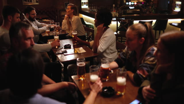 Diverse people drinking beer in the pub together video