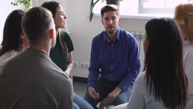 Diverse people sharing personal problems at psychotherapy session. Diverse people sitting in circle, sharing personal problems at psychotherapy session. Male psychologist therapist helping multiracial younger and older patients at group therapy, rehab concept. mental wellbeing stock videos & royalty-free footage