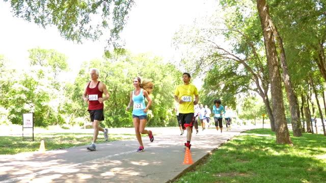 diverse race competitors running past during marathon or 5k charity race - välgörenhet bildbanksvideor och videomaterial från bakom kulisserna