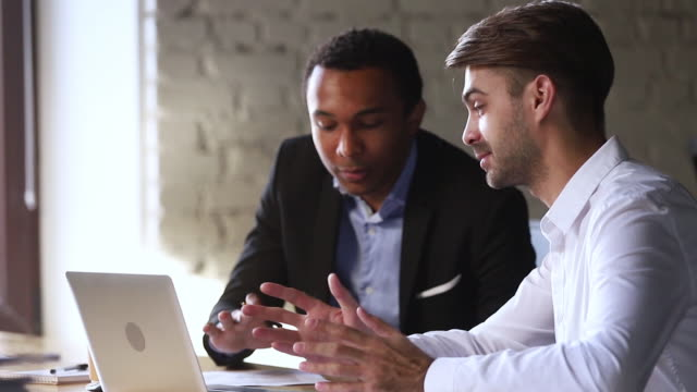 Diverse smiling manager and client having friendly conversation with laptop