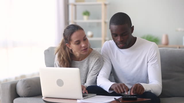 Diverse spouses manage family budget discuss loan agreement using computer