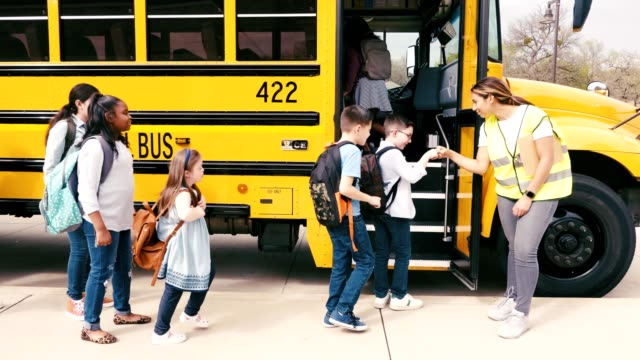 Diverse students board yellow school bus A cheerful female school bus driver gives elementary and middle school students fist bumps as they board the bus. persons with disabilities stock videos & royalty-free footage