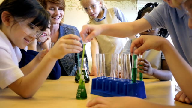 Diverse students in private elementary school science chemistry classroom conducting experiment video