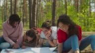 istock Diverse students making ecological project outdoors 1225785388
