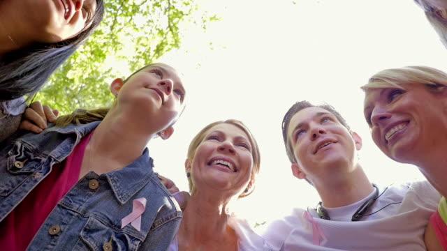zróżnicowany zespół huddled przed rozpoczęciem wyścigu na raka piersi cure zdarzenia - breast cancer awareness filmów i materiałów b-roll