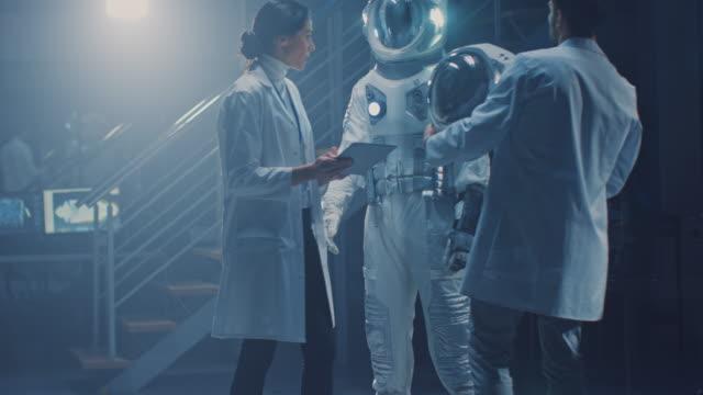 diverse teams von luft-und raumfahrt-wissenschaftlern und ingenieuren, die weiße mäntel tragen, haben diskussionen, benutzung von computern, design new space suit, die für galaxy exploration und reisen angepasst sind. astronaut bauen anzug - raumanzug stock-videos und b-roll-filmmaterial
