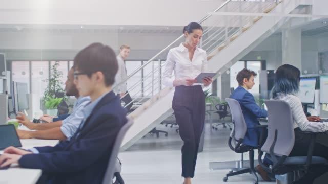 ein diges team von geschäftsmanagern und spezialisten arbeiten auf desktop-computern mit zwei rows of tables side by side. junge und motivierte geschäftsleute in modern open office. - employee stock-videos und b-roll-filmmaterial