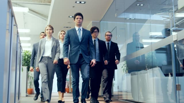 diverse team of delegates/ lawyers confidently marching through the corporate building hallway. multicultural crowd of resolute business people in stylish marble and glass offices. - business people stock videos & royalty-free footage
