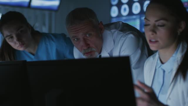 vielfältiges team von medizinern probleme lösen und punkt am computer bildschirme zeigen ct, mri-scans. neurologen / neurowissenschaftler arbeiten in brain research laboratory. - menschliche tätigkeit stock-videos und b-roll-filmmaterial