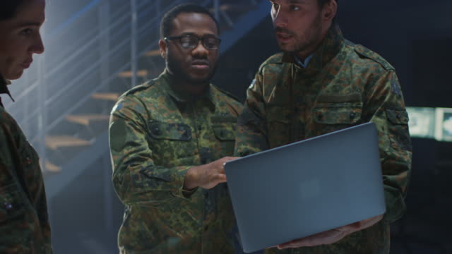 Diverse Team of Military Personnel Have Meeting in Top Secret Facility, Male SpecialistHolds Laptop Computer Talks with Officers. People in Uniform on Strategic Army Meeting
