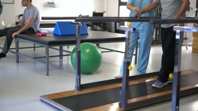 diverse team of physiotherapist doing therapy with a young patient and a senior patient - fisioterapia video stock e b–roll
