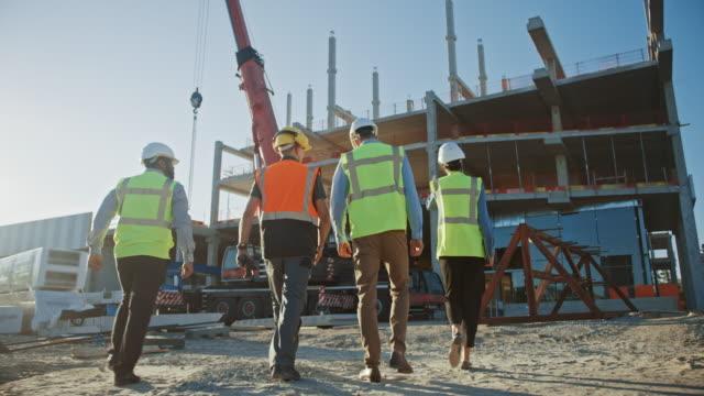 전문가의 다양한 팀은 상업, 산업 건물 건설 현장을 검사합니다. 토목 엔지니어, 투자자 및 근로자와 부동산 프로젝트. 배경 크레인, 마천루 어포워크 프레임 - 안전 스톡 비디오 및 b-롤 화면