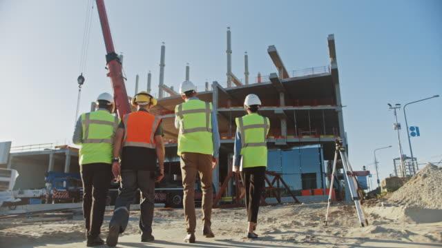 vídeos y material grabado en eventos de stock de diverso equipo de especialistas inspeccionan el sitio de construcción de edificios comerciales e industriales. proyecto inmobiliario con ingeniero civil, inversor y empresaria. en los marcos de encofrado de rascacielos de fondo - propiedad inmobiliaria