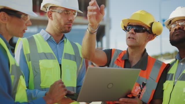 Diverses Team von Spezialisten verwenden Laptop-Computer auf der Baustelle. Immobilienbauprojekt mit Bauingenieur, Architekturinvestor, Geschäftsfrau und Arbeiter diskutieren Planplan – Video