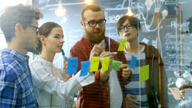 diverse team of young developers brainstorming, they have discussion and use glass board and sticky papers to conceptualize their new plan. creative people in stylish office environment. - post it video stock e b–roll