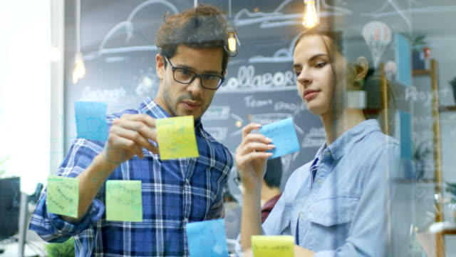 diverse team of young developers brainstorming, they have discussion and use glass board and sticky papers to conceptualize their new plan. creative people in stylish office environment. - progettare video stock e b–roll