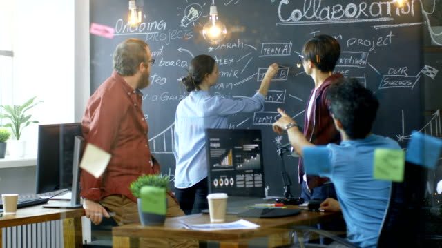 vídeos de stock e filmes b-roll de diverse team of young developers draw work plan on a blackboard wall, have heated discussion. creative office space with stylishly dressed people. - novo
