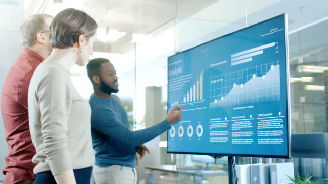 diverse team of young professionals in conference room have discussion about statistics and graphs shown on a presentation tv. - progettare video stock e b–roll