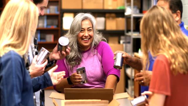 vídeos de stock e filmes b-roll de diverse team volunteering food drive - benefits
