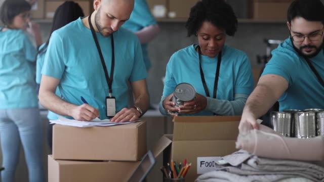 zróżnicowani wolontariusze pakujący pudełka z datkami w charytatywnym banku żywności - giving tuesday filmów i materiałów b-roll