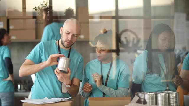 자선 푸드 뱅크에 기부 상자를 포장하는 다양한 자원 봉사자 - giving tuesday 스톡 비디오 및 b-롤 화면