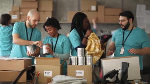 vídeos de stock e filmes b-roll de diverse volunteers packing donation boxes in charity food bank - comunidade