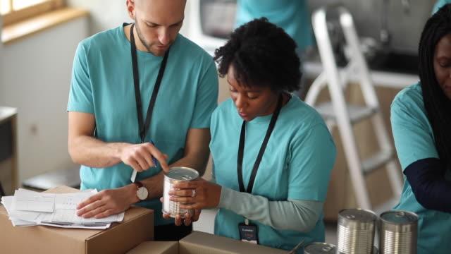 多元化志願者在慈善食品銀行包裝捐贈箱 - giving tuesday 個影片檔及 b 捲影像