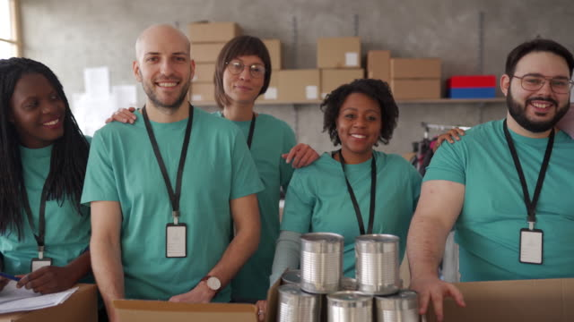 Diverse volunteers packing donation boxes in charity food bank Multi-ethnic group of people, diverse volunteers packing donation boxes in charity food bank. giving tuesday stock videos & royalty-free footage