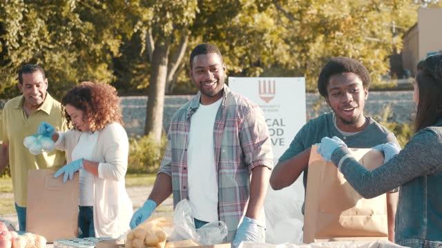 çeşitli gönüllüler açık gıda sürücü sırasında gıda bağışları ile sıralamak - giving tuesday stok videoları ve detay görüntü çekimi