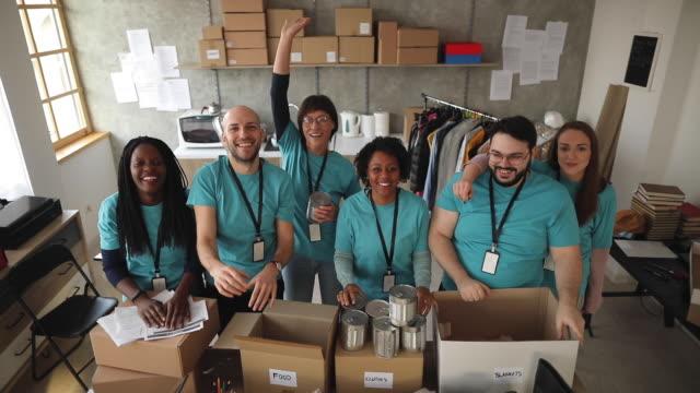 çeşitli gönüllüler yardım gıda bankasında size el sallayarak - giving tuesday stok videoları ve detay görüntü çekimi