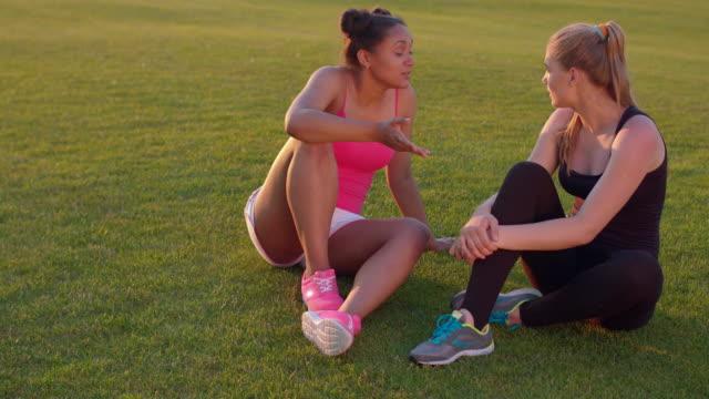 Diverse women friends. Sport girls talking outdoors. Young women on grass video