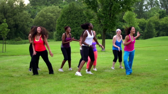 Diverse women wearing colorful clothing doing Zumba in suburban park video