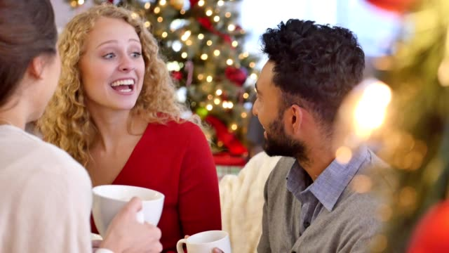 Diverse young adults enjoy a cup of coffee while talking during Christmas celebration video