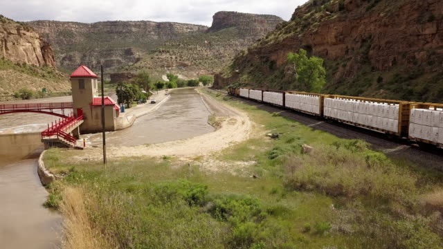 A Diversion Dam on the Colorado River Diverting water to create an irrigation canal system for farming and ranching with a freight train speeding past