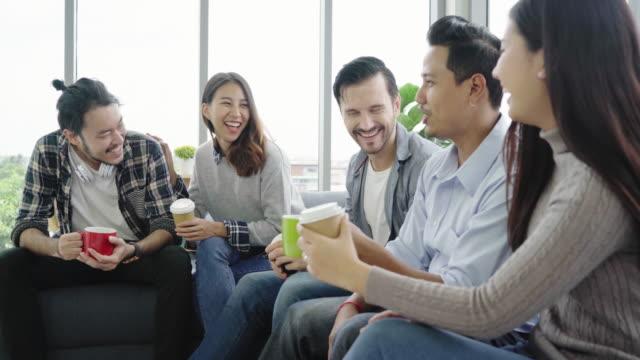 コーヒー カップを保持している、オフィスのソファに座って笑顔で何かを議論する若者グループ チームの多様性。クリエイティブ ・ オフィスでの休憩時間。 - お茶の時間点の映像素材/bロール