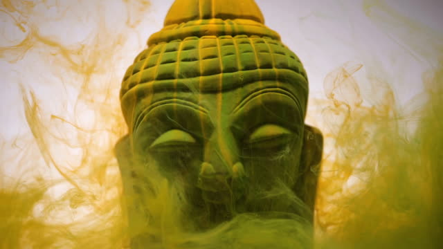 Divine Buddha Statue Surreal ink / smoke in yellow, flowing over Buddha idol buddha stock videos & royalty-free footage