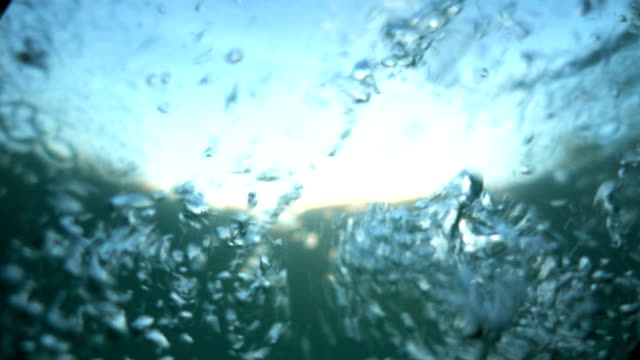 diving into the water. falling into the water in slow motion. different-sized bubbles in foaming turquoise water. sinking. version1. - tuffarsi video stock e b–roll