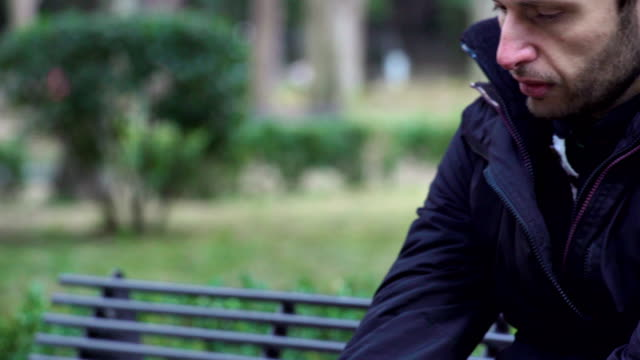 divorced man is in despair sitting on the bench in a park video