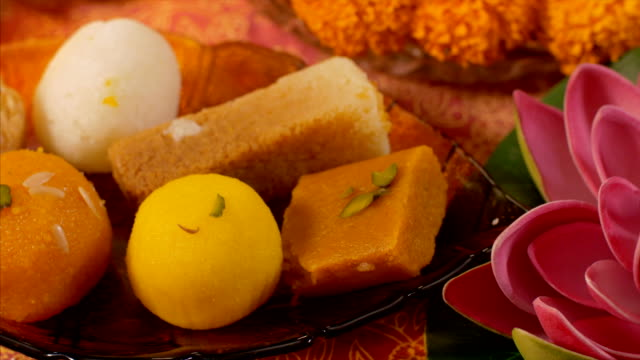 celebrazione di diwali - tavolo decorato con dolci, diya e fiori per puja / preghiera - dolci video stock e b–roll