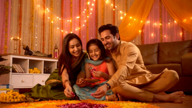 Diwali festival - An Indian nuclear happy family making Rangoli with flowers petal and loving their daughter Indian stock video of a happy family celebrating Diwali festival in their new apartment indian family stock videos & royalty-free footage
