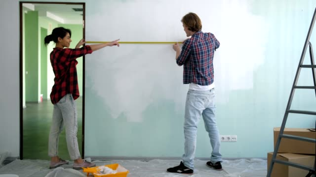 Diy couple measuring wall with measuring tape Rear view of positive multiracial couple measuring wall with measuring tape during renewal of interior design in new apartment. Joyful renovation family with measure tape checking wall length in room. instrument of measurement stock videos & royalty-free footage