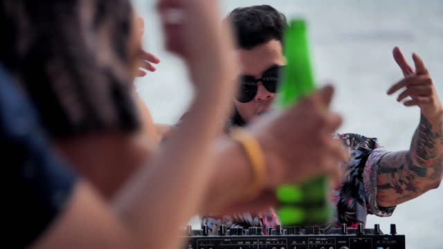 Dj mixing at sunset beach party in summer vacation outdoor on the beach.DJ playing and mixing music for crowd people.Hands of a DJ on vinyl and mixer knobs.Vacations - iStock