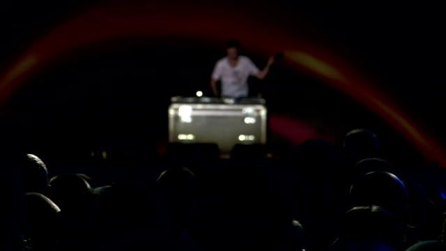 Dj playing track in front of crowd on illuminated stage video