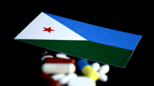 Djibouti flag with lot of medical pills isolated on black background Djibouti flag with lot of medical pills isolated on black background horn of africa stock videos & royalty-free footage