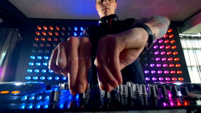 DJs fingers turning small mixer knobs. video