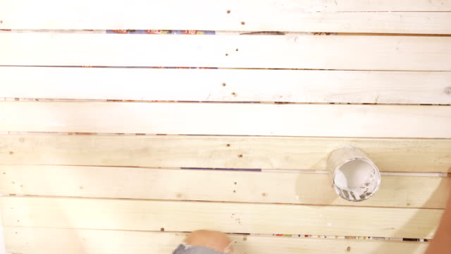 DIY do it yourself footage of wooden boards being painted in white video