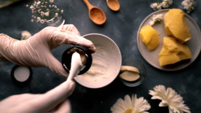 do it yourself - herstellung von hausgemachten bio-handcreme - füllung leere tasse mit creme mit porzellan löffel dann abschlussbox - selbstgemacht stock-videos und b-roll-filmmaterial