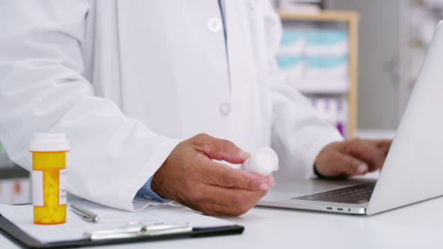 I do written and digital prescriptions 4k video footage of a pharmacist using a laptop while holding medication pharmacist stock videos & royalty-free footage